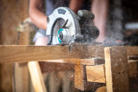 A worker saws a wooden beam. Building a house.
