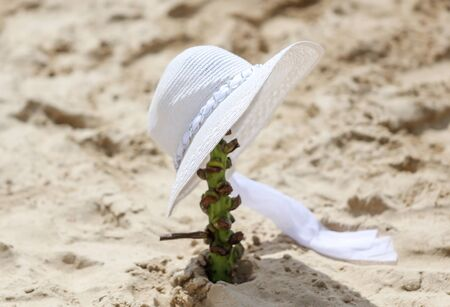 White hat in the sand on the shore of the sea beach.