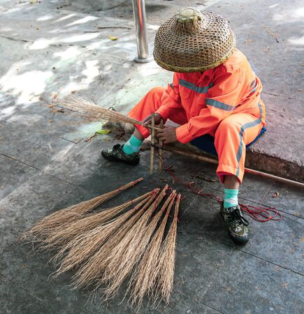 Janitor with a broom on a city street.