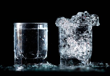 Splashes and drops of blue water in two glasses are isolated on a black background.
