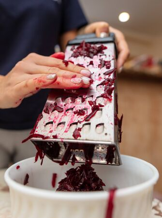 Girl cuts boiled red beets on a grater. Cooking food