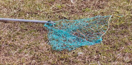 Landing net on the shore of the pond. Inventory of the fisherman Stock Photo