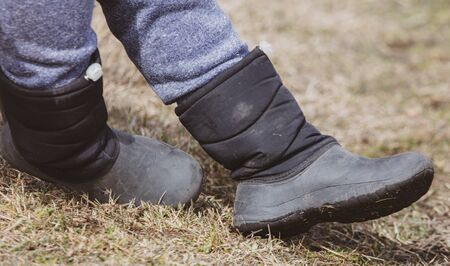 Boots on the feet of a boy on the grass in early spring.