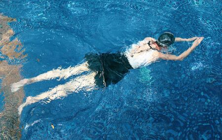 The girl swims underwater in the pool. Immersion under water with holding your breath.