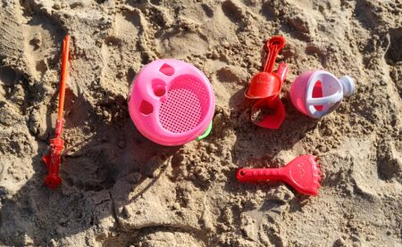 Building of sand with a toy shovel and a bucket near the sea. Rest in the resort. Фото со стока