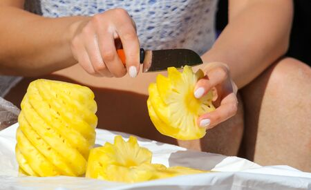 Knife sliced pineapple on a table. Fruit in the tropics.