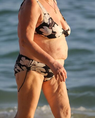 Fat woman in a swimsuit on the seashore. Rest at the resort.