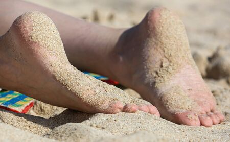 Close-up of a girl's foot in the sand on a beach.