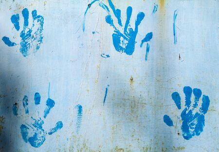 Handprint of blue paint on the wall. Background