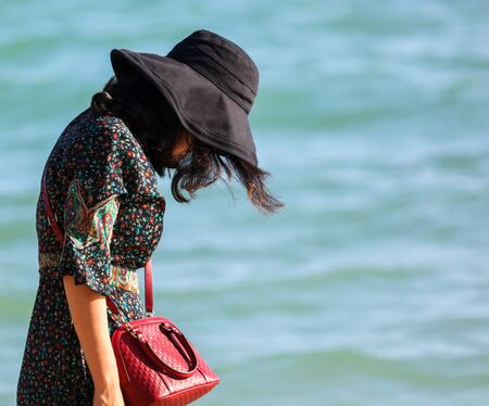 A girl in a dress with a handbag walks on the seashore. Rest at the resort.