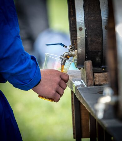 A man pours beer into a glass with a wooden barrel. Hops Drink Reklamní fotografie