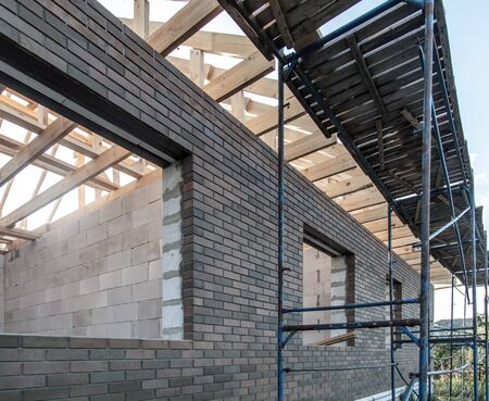 The construction of metal and boards near the wall. Home construction Standard-Bild