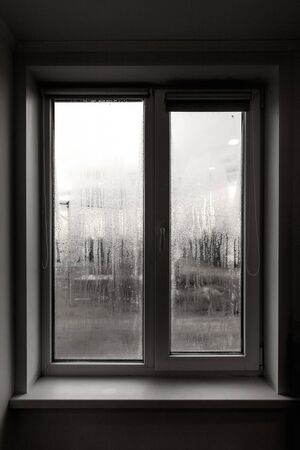 A window with fogged glass in the room as a backdrop. Banque d'images