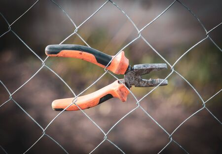 Pliers are hanging on a metal mesh fence.