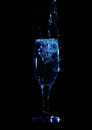 Splashes and drops of blue water in a glass are isolated on a black background. Banque d'images - 150189678