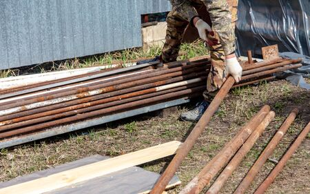 Worker works with metal pipes at a construction site at home.