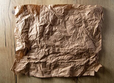 Crumpled paper on a wooden background.