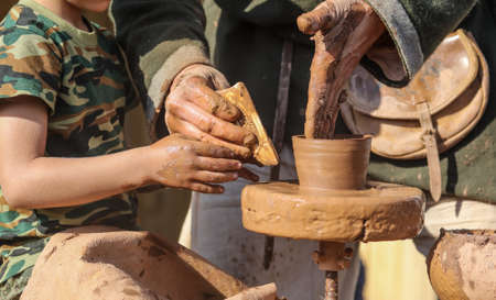 Hands of a boy and a man sculpt clay dishes. The ancient method of making dishes.