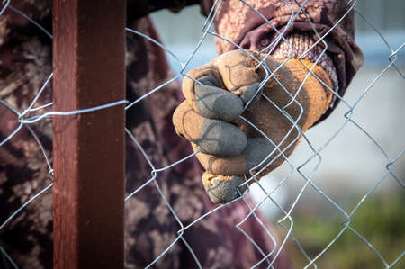 A man sets his hands a metal mesh on the fence.