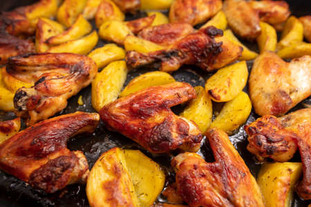 Baked chicken and potatoes in the oven as a background. Cooking food.