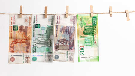 Russian rubles hang on a rope on a white background.