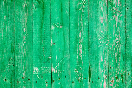 Wooden boards on an old green fence as an abstract background. Texture.