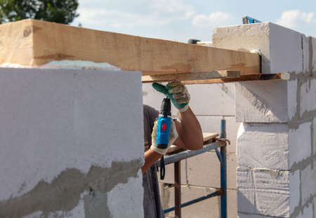 A worker builds the walls of a house from aerated concrete bricks. Technology