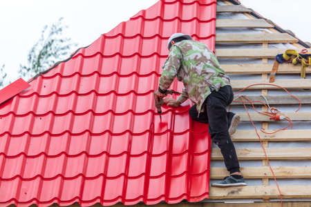 Workers install red metal tiles on the roof of the house.