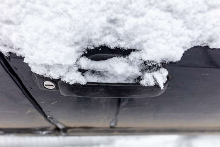 Frozen car door handle in winter. Snow