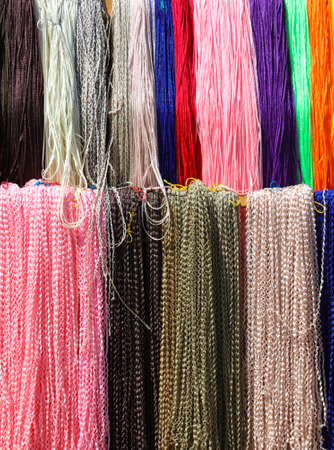 Multi-colored threads for braiding hair. Background