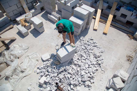 A worker cuts aerated concrete bricks with a saw. Technology 写真素材