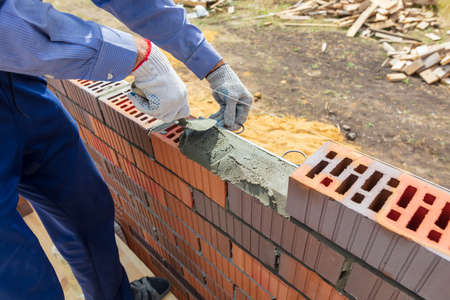 The worker lays bricks on the wall of the house. Construction