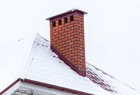 Brick chimney in the snow on the roof of the house. Winter