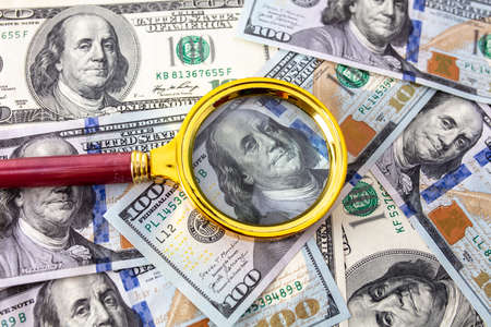 Close-up of one hundred dollars in a magnifying glass on the table.