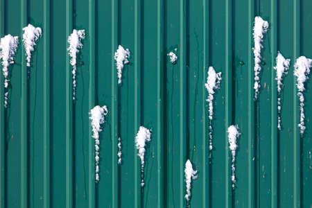 Snow on the roof of the house. Green roof tiles 版權商用圖片