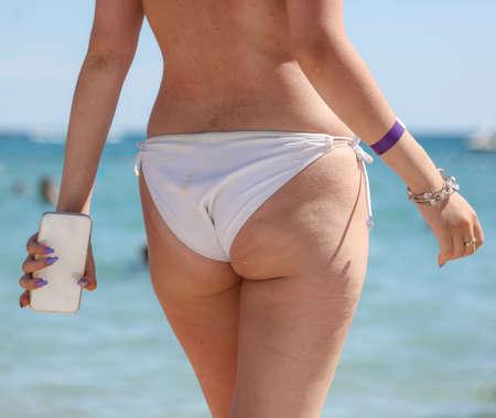 Girl in a swimsuit on the beach near the sea. Foto de archivo