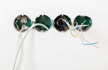Wires from a junction box on a white wall. Repairs Reklamní fotografie