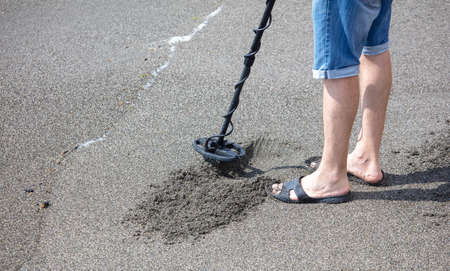 A man with a metal detector on the seashore.