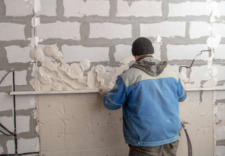 A worker plasters the walls in the room. Building a house Stock fotó