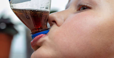 Boy drinks a drink from a plastic bottle. Close-up.