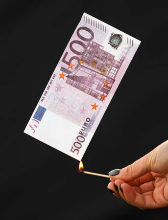 Five hundred Euros burn from a match isolated on a black background. Banco de Imagens