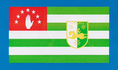 Flag of Abkhazia on a blue background. Banco de Imagens - 167321400
