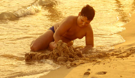A boy plays in the sand on the seashore. Banco de Imagens - 167321700