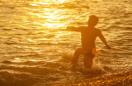 Boy swims in the sea with splashes at sunset.