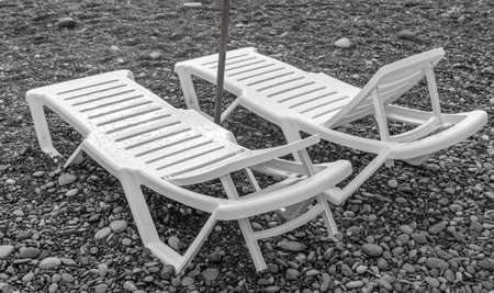 Sun loungers on a pebble beach by the sea. Banco de Imagens - 167322264