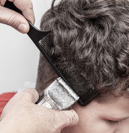 The hairdresser cuts the hair of a boy with a machine.