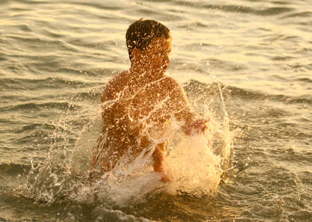 Boy swims in the sea with splashes at sunset. Banco de Imagens - 167322015