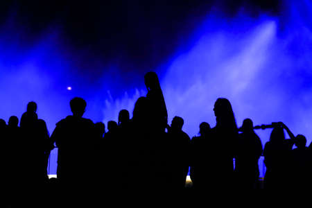 Silhouettes of people at the blue fountain at night. Background Banco de Imagens - 167320831