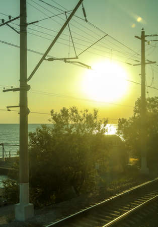 Poles with electric wires near the railway at sunset. Banco de Imagens