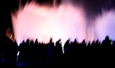 Silhouettes of people in motion near a colored fountain at night. Background Banco de Imagens - 167320847